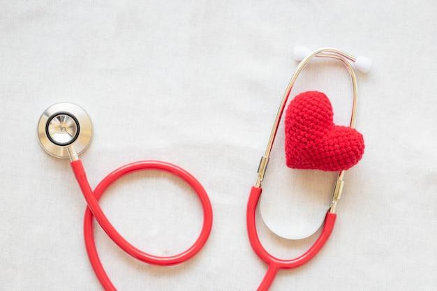 Coração e estetoscópio vermelhos. conceito de saúde cardíaca, cardiologia, dia mundial do coração, hipertensão.