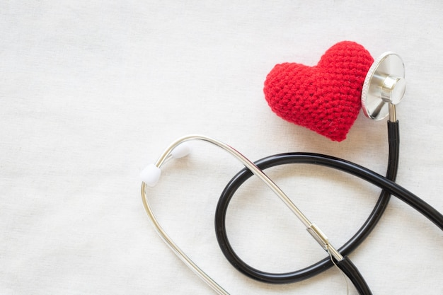Coração e estetoscópio vermelhos em fundo branco isolado, copie o espaço