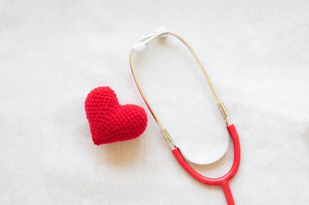 Coração e estetoscópio vermelhos. saúde do coração, cardiologia, plano de seguro, dia do médico, dia mundial do coração.