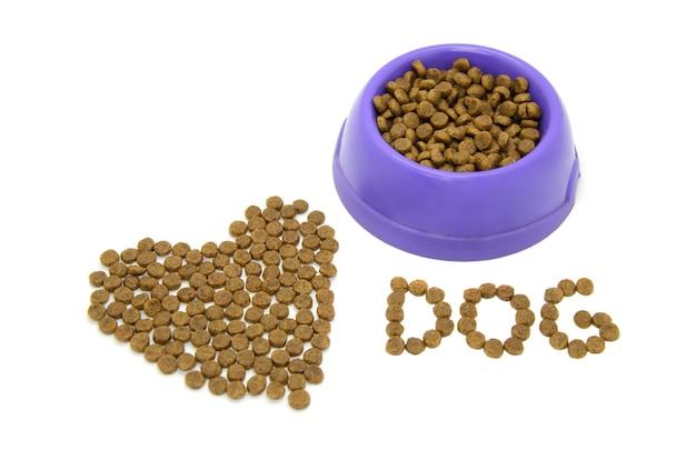 Coração e palavra cão forrados com comida de animal seca, tigela de plástico cheia de comida isolada no branco