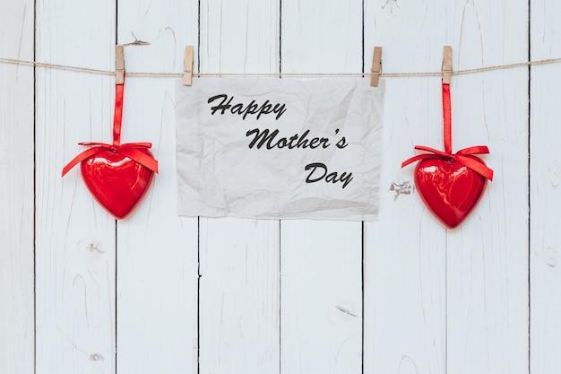 Coração e papel pendurado no presente de madeira branca, conceito do dia das mães.