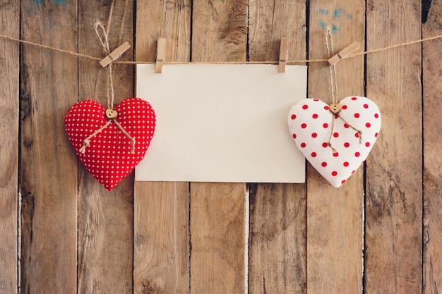 Coração e papel vazio que pendura no fundo de madeira com espaço da cópia.