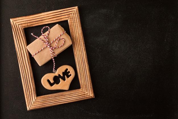 Coração e presente na moldura de madeira