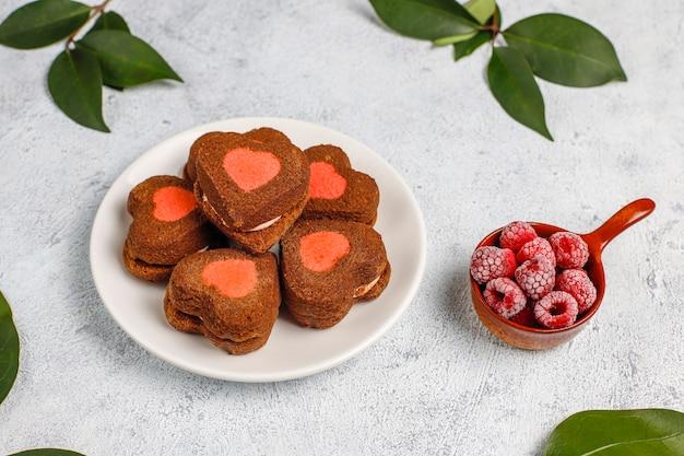 Coração em forma de biscoitos dos namorados com framboesas congeladas na luz de fundo