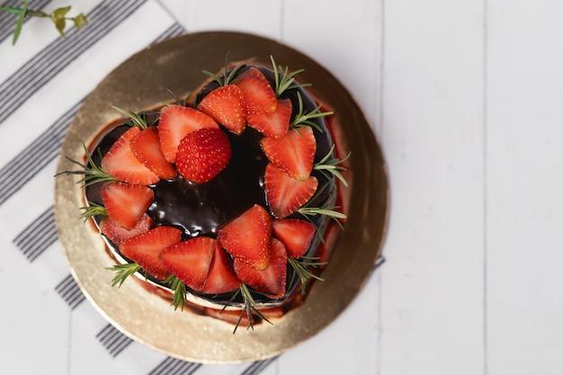 Coração em forma de bolo de chocolate delicioso com morangos no fundo branco para o conceito de alimentos e padaria