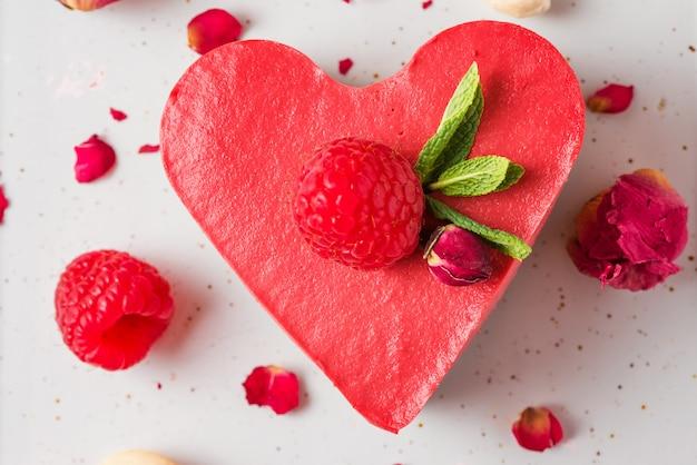 Coração em forma de bolo vegetariano vermelho cru com framboesas frescas, hortelã e flores secas. sobremesa de dia dos namorados. vista do topo