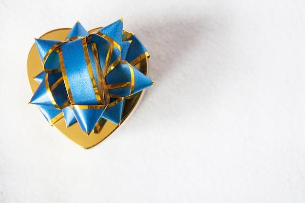Coração em forma de caixa de presente de natal em fundo de neve. caixa de presente dourada para o ano novo.