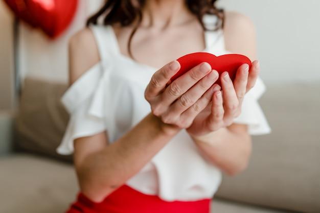 Coração em forma de cartão vermelho dos namorados nas mãos da mulher no sofá em casa