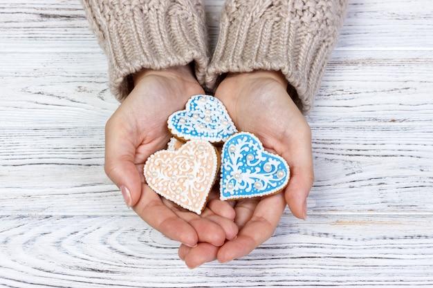 Coração em forma de cookie em cookies de férias de mãos de mulher