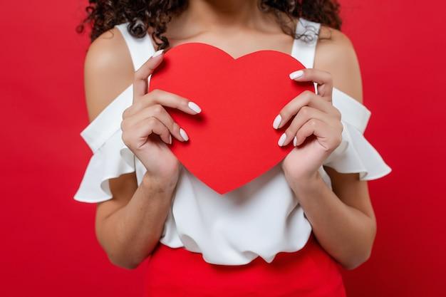 Coração em forma de coração dia dos namorados nas mãos de mulher negra, vestindo blusa branca isolada sobre vermelho