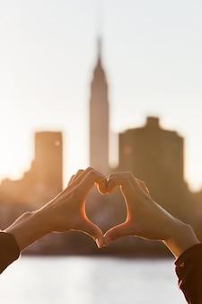 Coração em forma de mãos ao pôr do sol, horizonte de nova york