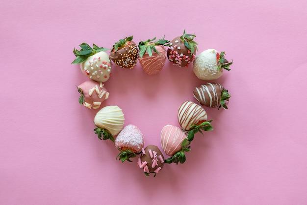 Coração em forma de morangos cobertos de chocolate artesanais com diferentes coberturas em fundo rosa