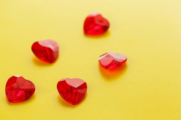 Coração em forma de padrão de cristais vermelhos na superfície amarela, corações de geléia crisscallic na parte superior, vista de cima