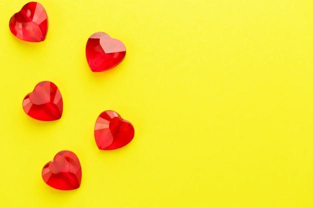Coração em forma de padrão de cristais vermelhos na superfície amarela