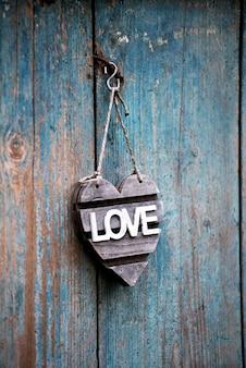 Coração em forma de sinal de amor pendurado em uma porta velha