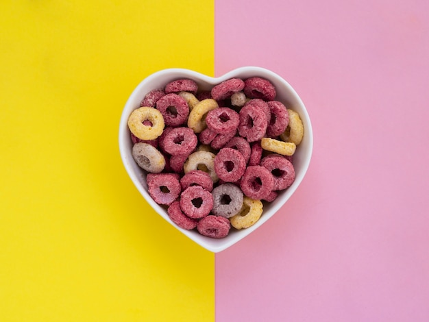 Coração em forma de tigela cheia de loops de frutas-de-rosa e amarelas