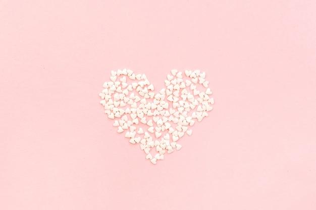Coração em fundo rosa pálido. flat lay, top view conceito de amor.
