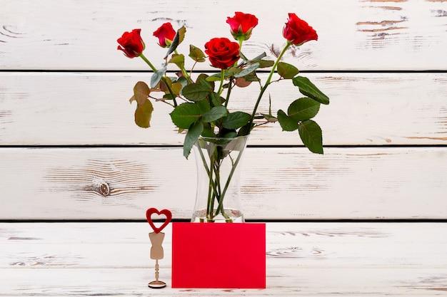 Coração em pé e rosas cumprimentando coração de papel e flores enviam votos de felicidades, o amor está por toda parte