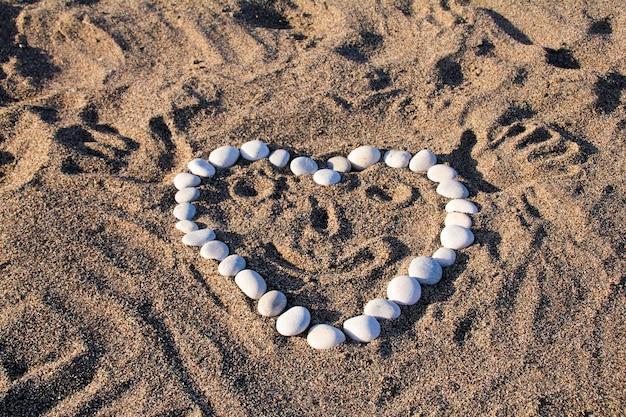 Coração engraçado na areia da praia