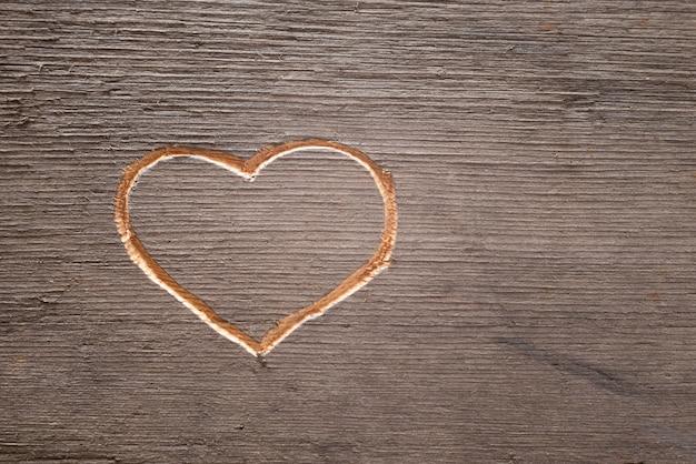 Coração esculpido na prancha de madeira.