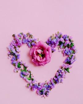 Coração feita com lavanda e flor rosa em fundo rosa