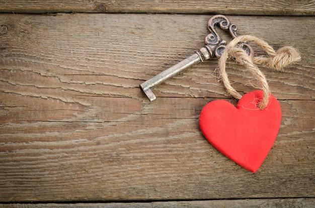 Coração feito à mão com chave junto deitado sobre uma placa de madeira. vista do topo