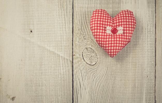 Coração feito à mão no fundo de madeira branco. cores suaves vintage