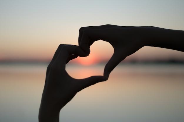 Coração feito com a mão e o sol é o pano de fundo.