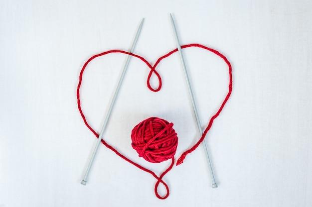 Coração feito da linha com as agulhas de lã do fio e de confecção de malhas no fundo de madeira branco.