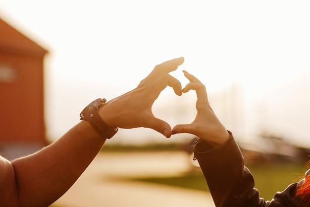 Coração feito das mãos de um cara e uma garota ao pôr do sol