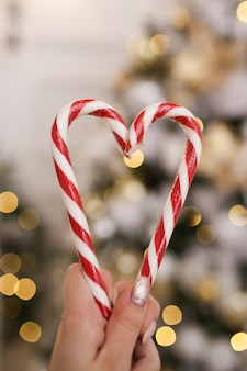 Coração feito de bastões de doces de natal em um fundo de bokeh e guirlandas