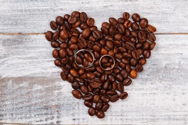 Coração feito de café e anéis de casamento.