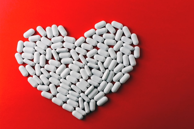 Coração feito de comprimidos brancos sobre fundo vermelho, medicamentos para doenças cardíacas