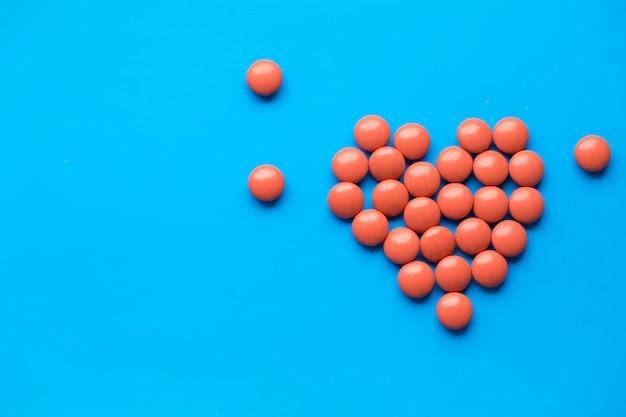 Coração feito de comprimidos em fundo azul. comprimidos com copyspace. pare o coronavirus