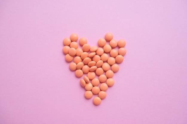 Coração feito de comprimidos laranja de garrafa de vidro. epidemia, analgésicos, cuidados de saúde, comprimidos de tratamento e conceito de abuso de drogas. vista do topo. flatlay.