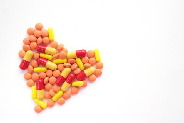Coração feito de comprimidos multicoloridos. epidemia, analgésicos, cuidados de saúde, comprimidos de tratamento e conceito de abuso de drogas. vista do topo. flatlay