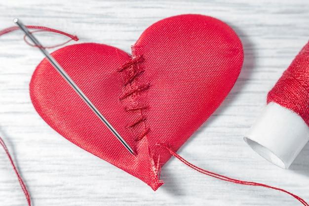 Coração feito de duas metades em uma mesa de madeira branca. ao lado, há uma agulha com uma linha roscada e um carretel com linhas vermelhas.