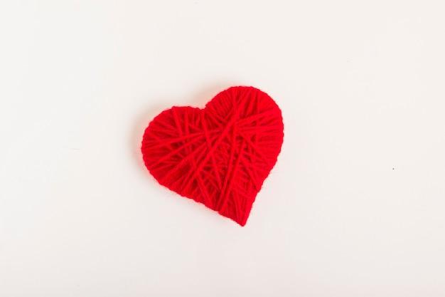 Coração feito de fios de lã em um fundo branco