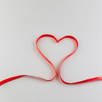 Coração feito de fita de cetim vermelho