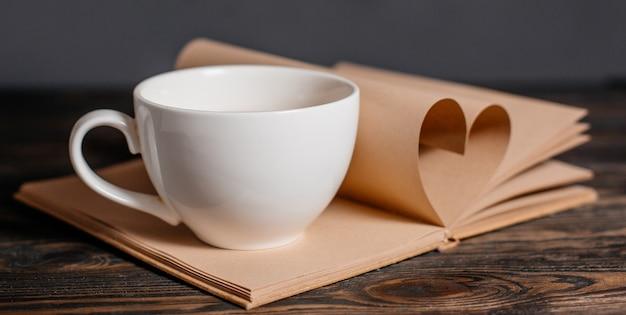 Coração feito de folhas de livro com uma xícara em uma mesa de madeira