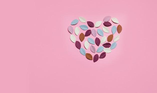 Coração feito de folhas de papel multicoloridas em um fundo rosa.