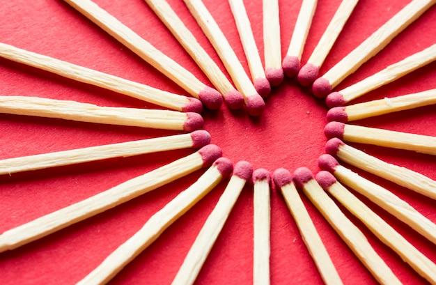 Coração feito de fósforos na superfície vermelha. amor. cartão postal do dia dos namorados. conceito de amor para o dia das mães com espaço para texto