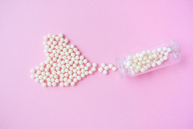 Coração feito de glóbulos homeopáticos e frasco de vidro na cor rosa