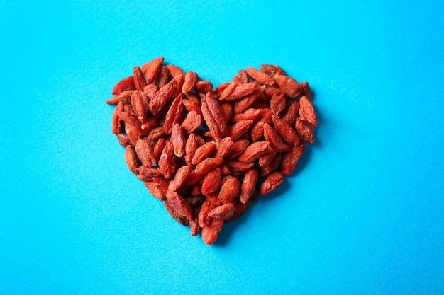Coração feito de goji berries no espaço de cor