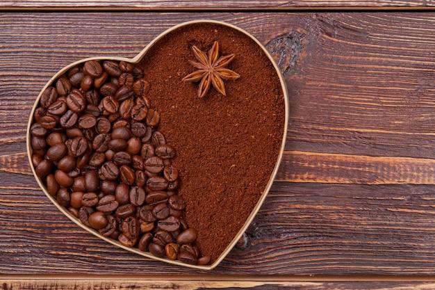 Coração feito de grãos de café e café instantâneo. anis no café instantâneo marrom. superfície de madeira marrom.