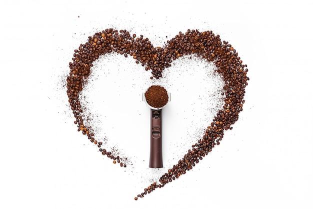 Coração feito de grãos de café torrados e café moído em uma superfície branca no centro, encontra-se um suporte cheio de café moído