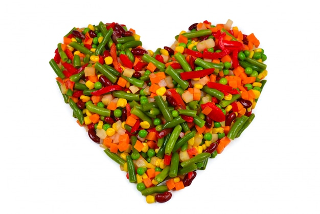 Coração feito de legumes. milho, cenoura, pimentão, feijão verde. isolado no branco