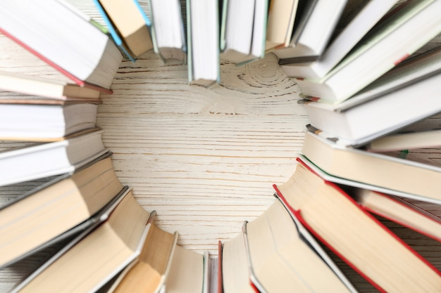 Coração feito de livros sobre espaço rústico de madeira branco, vista superior