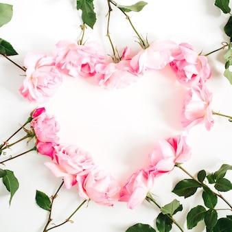 Coração feito de rosas cor de rosa em fundo branco. camada plana, vista superior. estampa floral