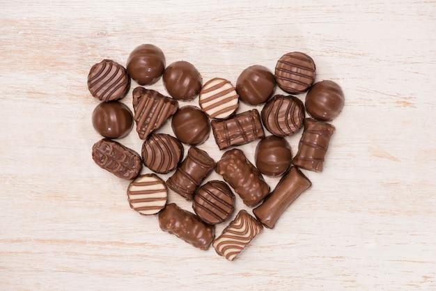 Coração feito de trufas de chocolate com fundo de madeira.